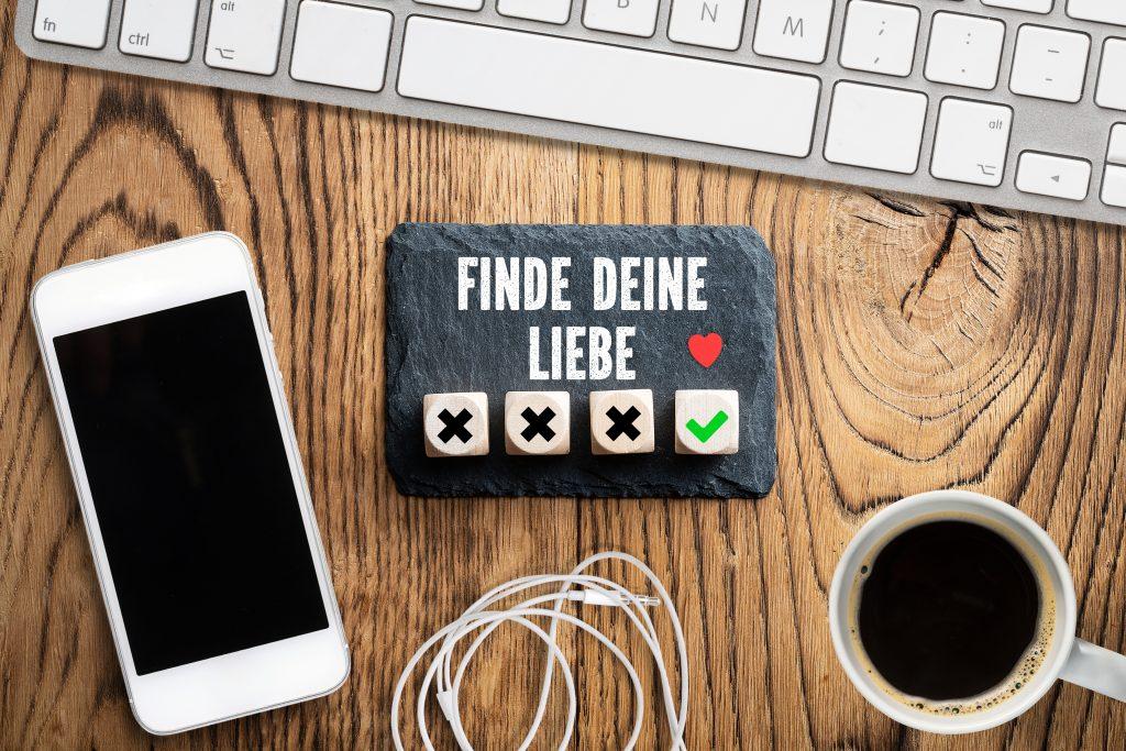 """Tastatur und Smartphone auf einem Holztisch, dazwischen eine Schieferplatte mit der Nachricht """"Finde Deine Liebe"""""""