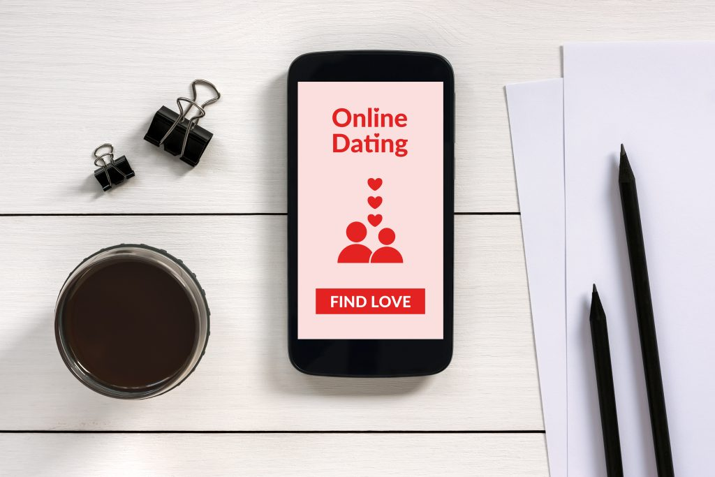 Online-Dating App auf einem Smartphone, welches auf einem Tisch mit weiteren Utensilien liegt