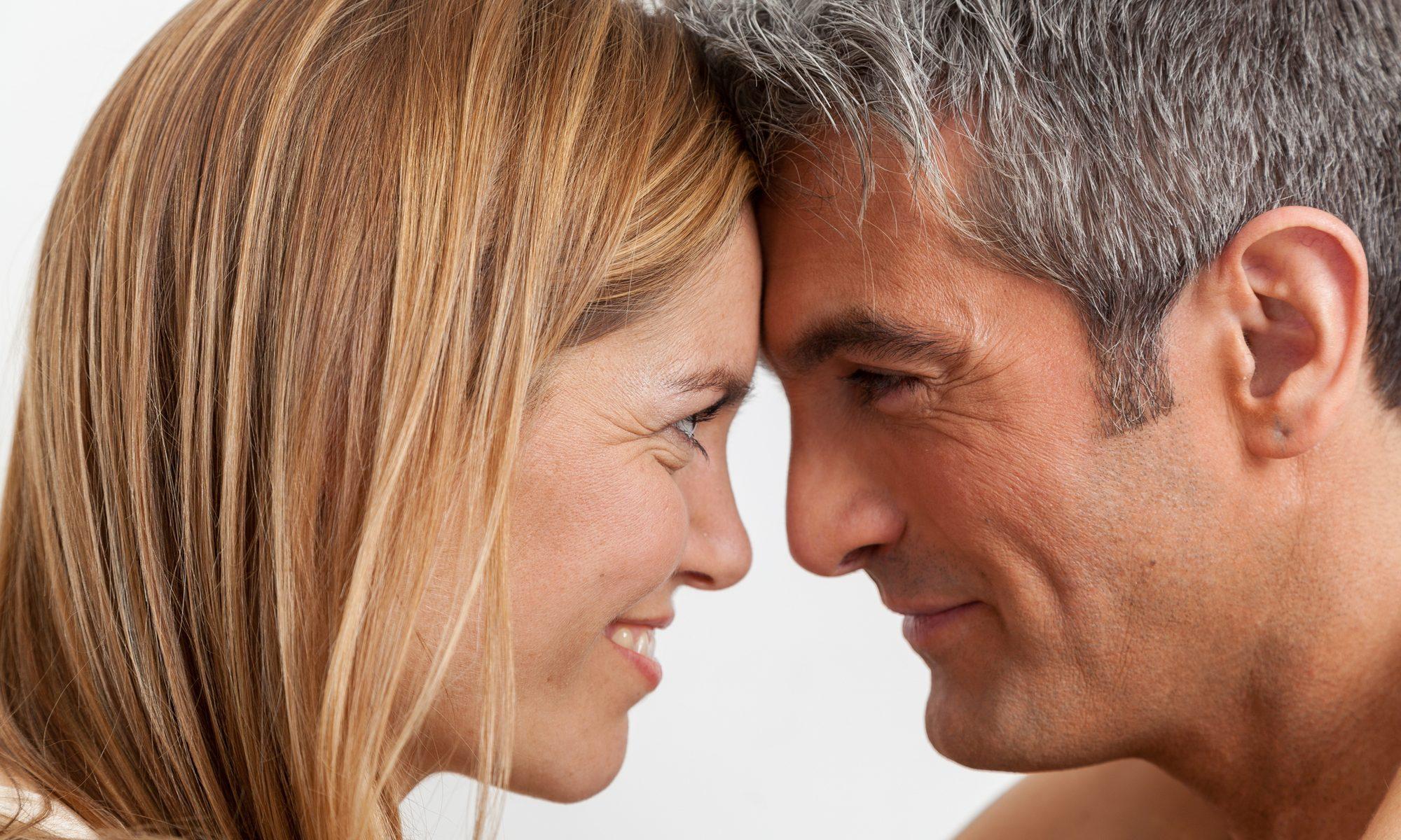 Paar mittleren Alters lächelt sich Kopf an Kopf an