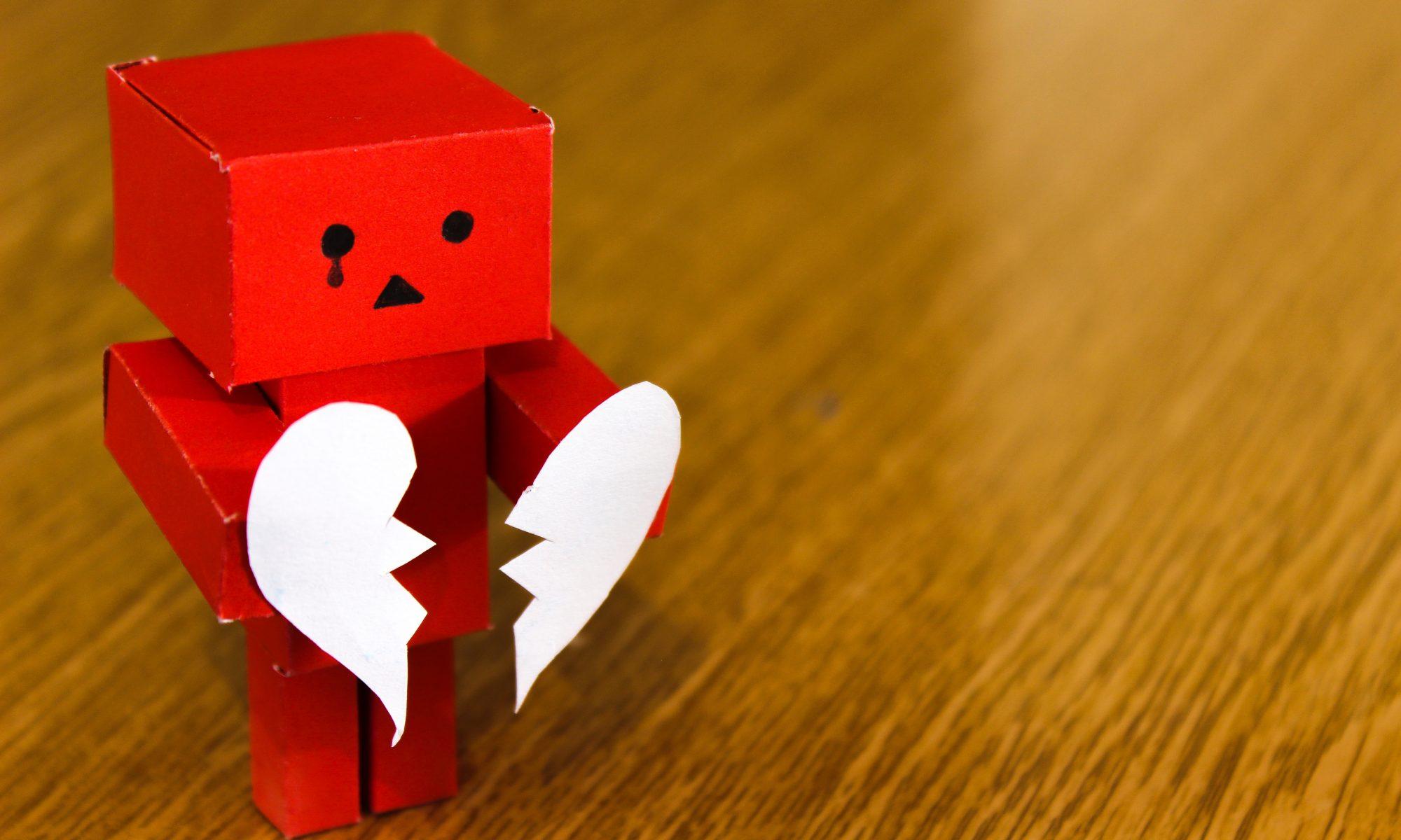 Rotes Pappmännchen mit gebrochenen Herz in der Hand