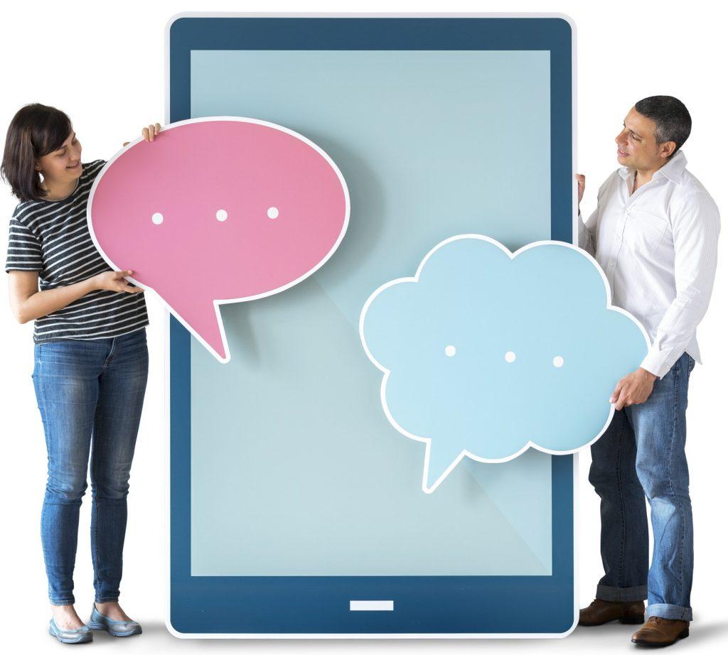 Mann und Frau stehen vor großem Tablet, mit Sprechblasen in der Hand