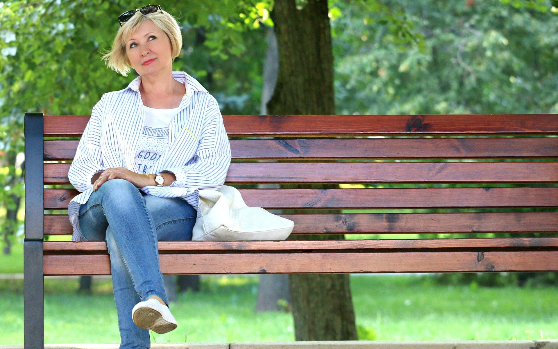 Frau mittleren alters, sittz alleine auf einer Parkbank