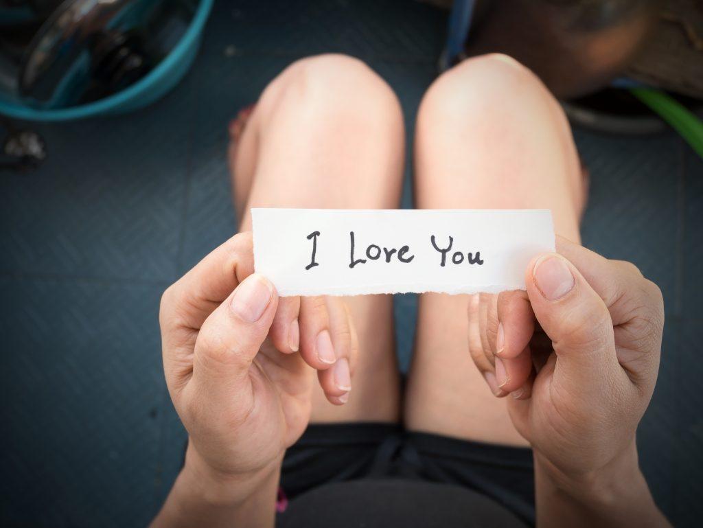 "Frau hält Zettel mit ""I love You"" in der hand"