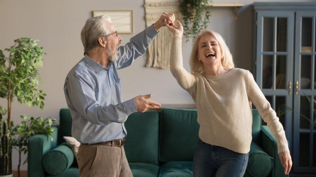Älteres Paar tanzt fröhlich im Wohnzimmer