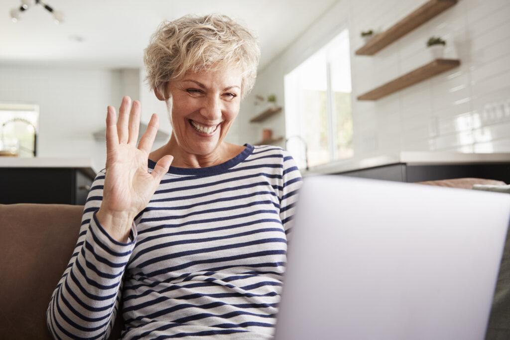 Frau winkt fröhlich im Video-Call