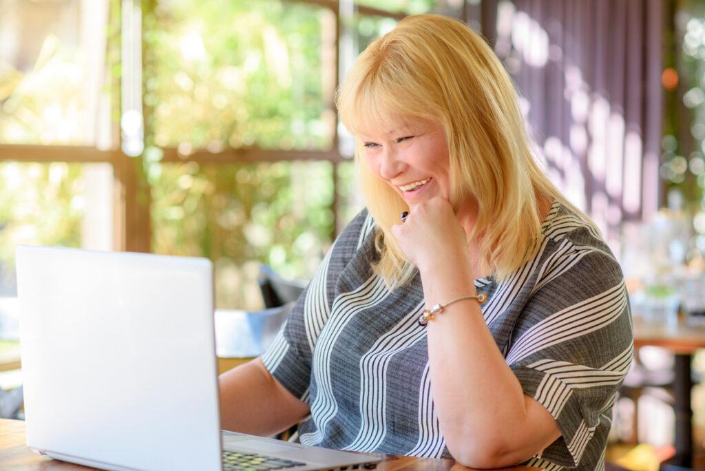 Frau sitzt vor dem Laptop und macht online dating