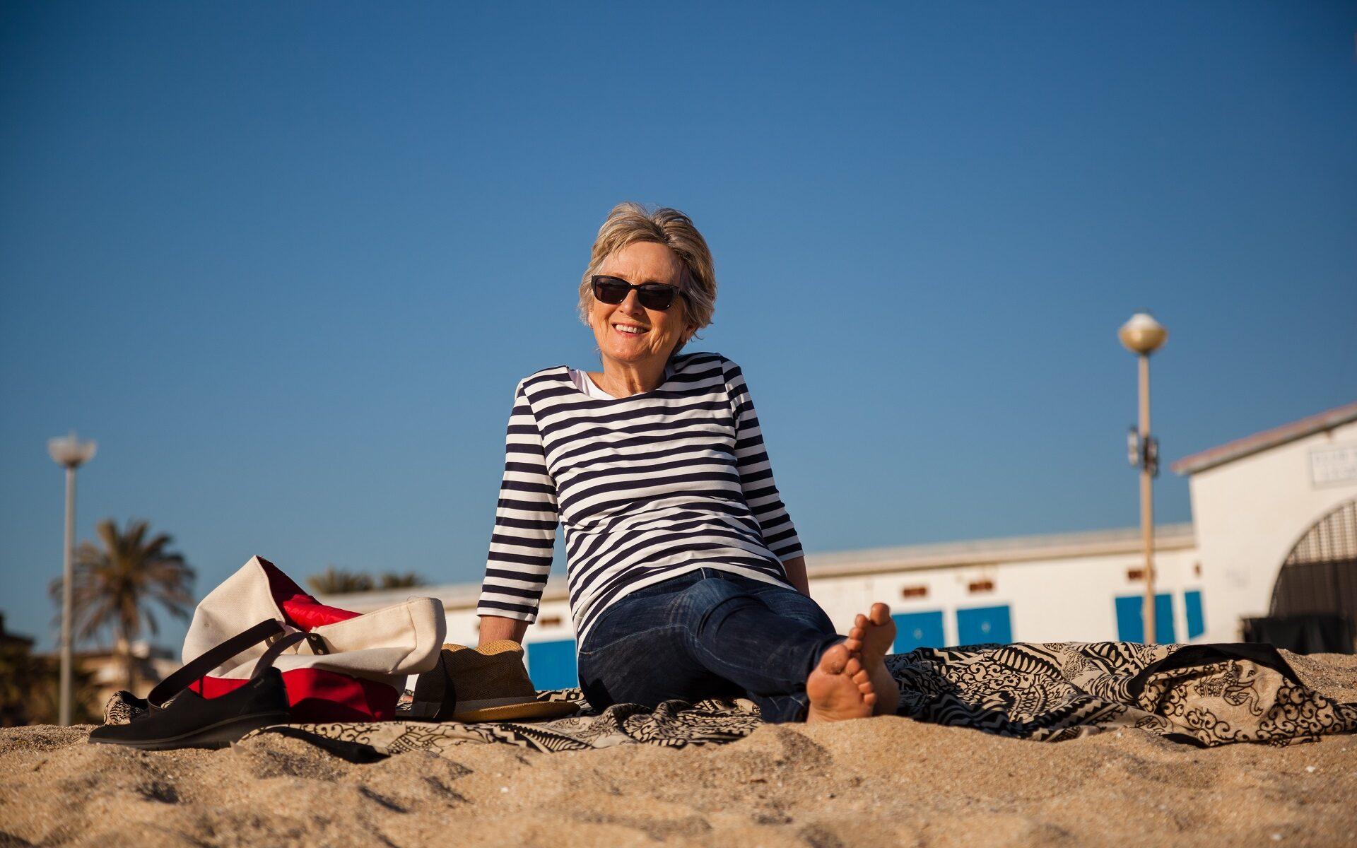 Single Frau sitzt fröhlich am Strand
