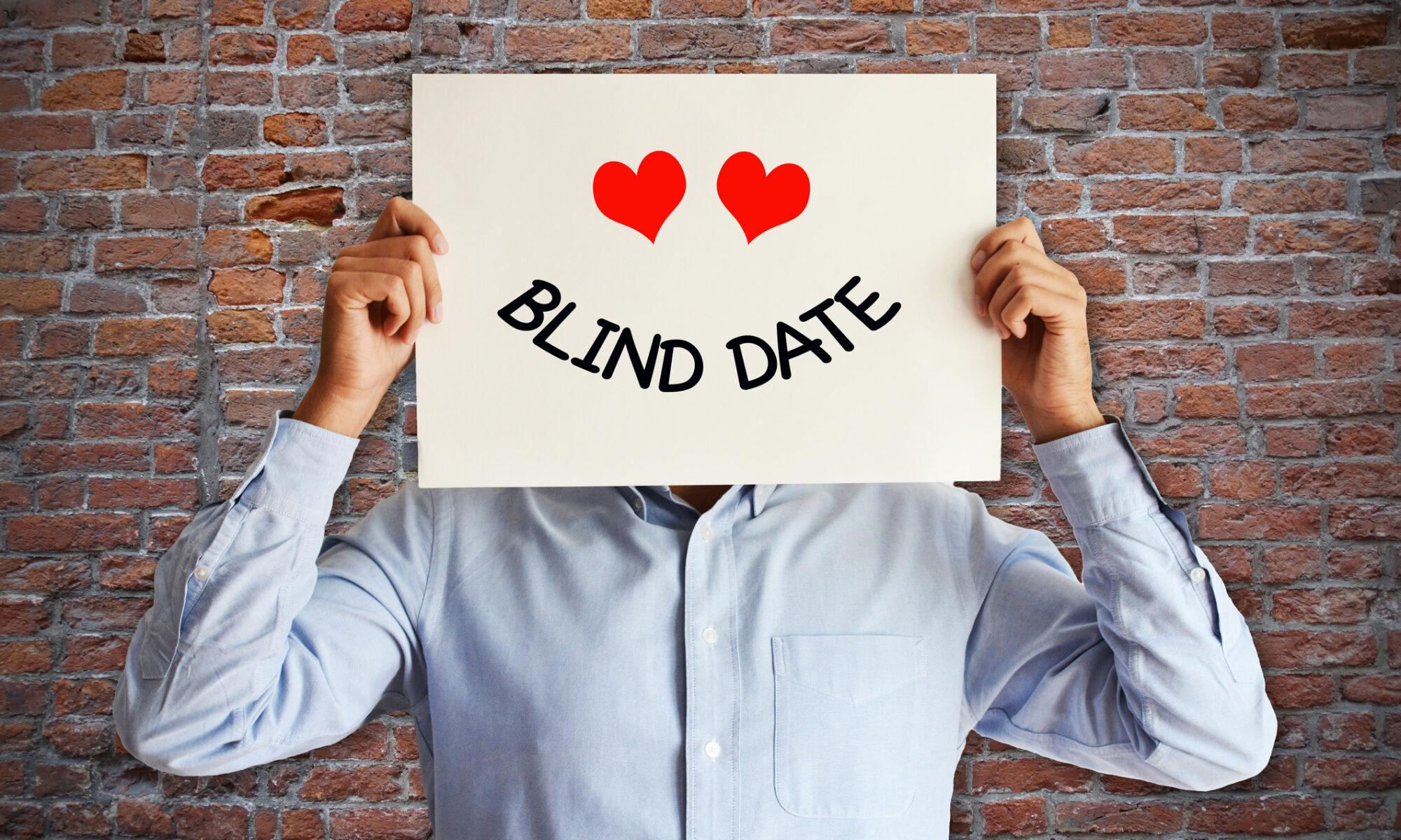Mann hält sich ein Blind Date Schild vor dem Kopf